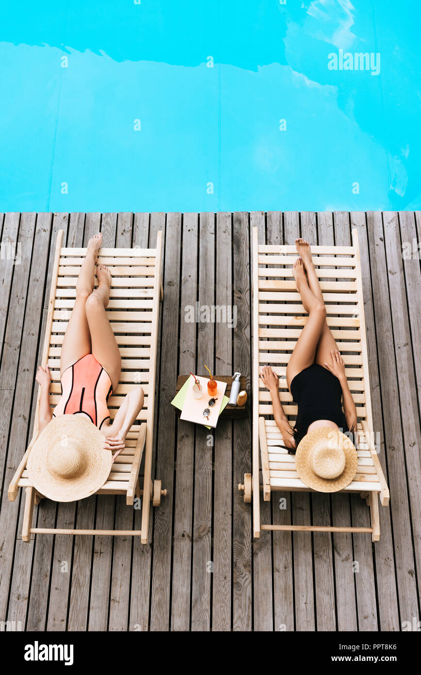 high angle view of young women in swimwear and hats lying on chaise lounges near swimming pool - Stock Image