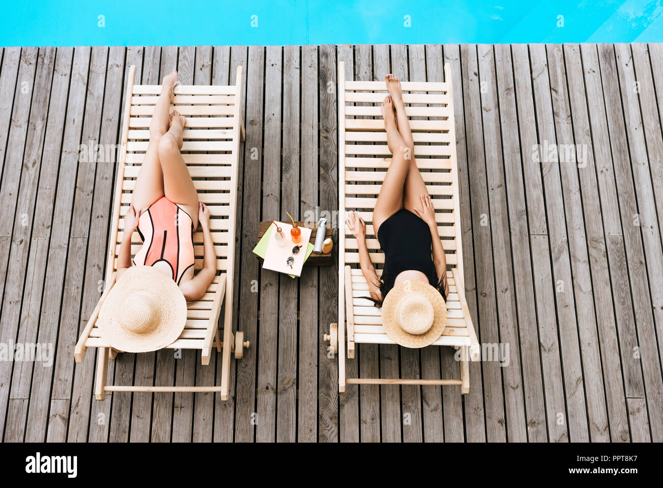 young women in swimsuits and hats lying on chaise lounges near swimming pool - Stock Image