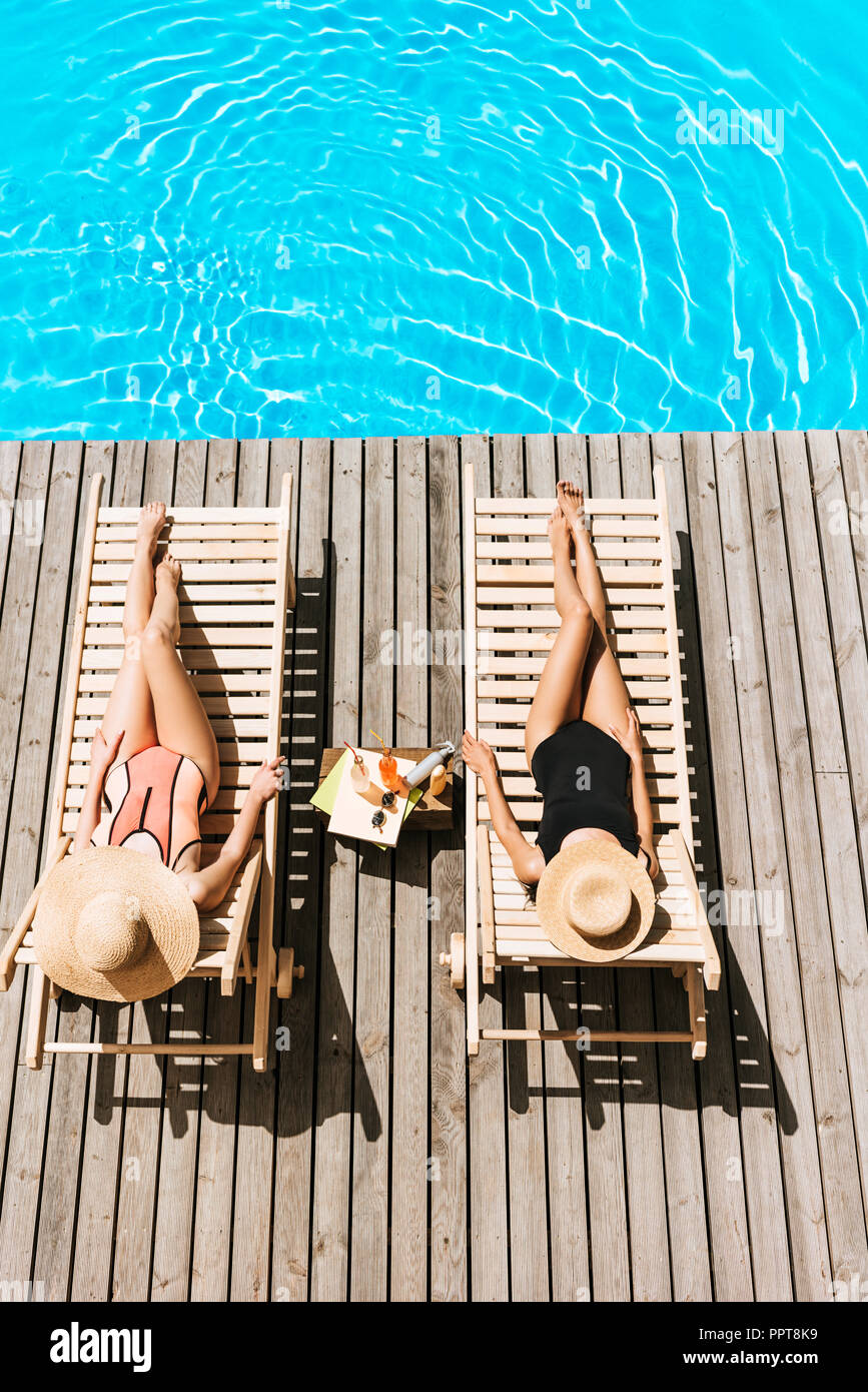 high angle view of young girlfriends lying on chaise lounges near swimming pool - Stock Image