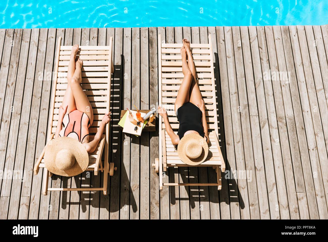 high angle view of young women resting on chaise lounges near swimming pool - Stock Image