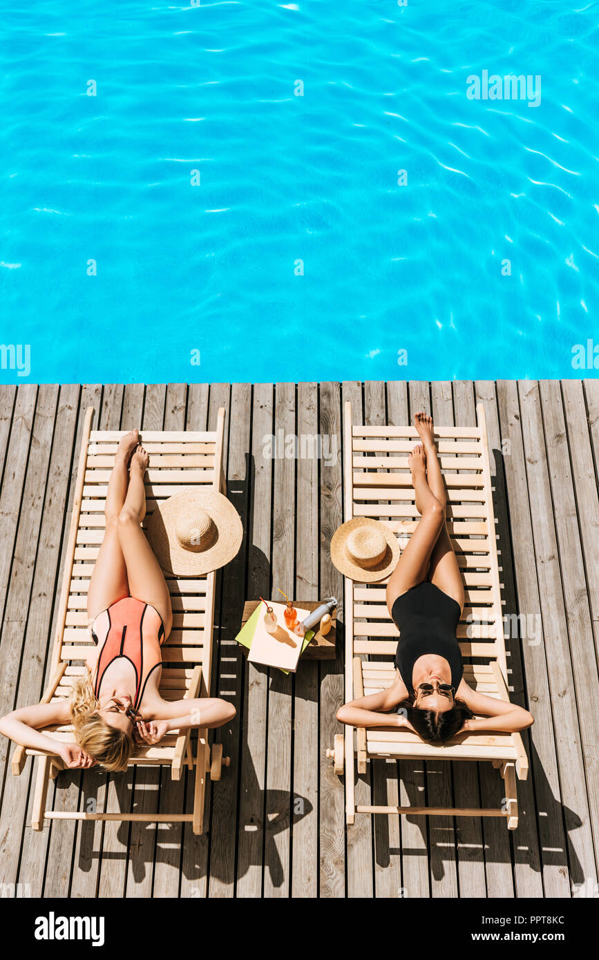 high angle view of young women tanning on chaise lounges near swimming pool - Stock Image