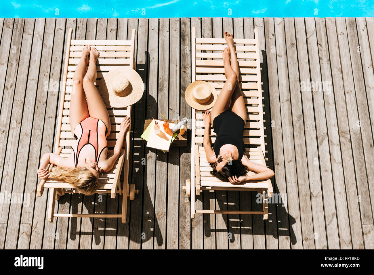 top view of young women tanning on chaise lounges near swimming pool - Stock Image