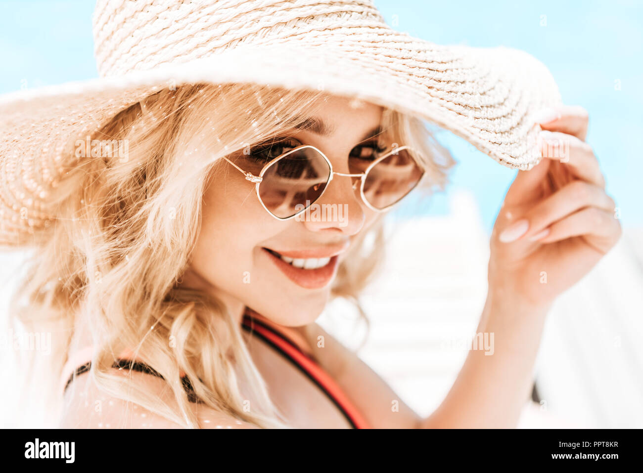 portrait of beautiful young blonde woman in wicker hat and sunglasses smiling at camera near pool - Stock Image