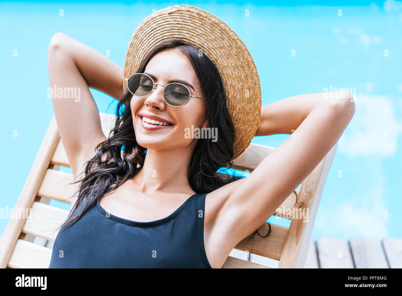 beautiful young brunette woman in swimsuit, straw hat and sunglasses resting with hands behind head at poolside - Stock Image