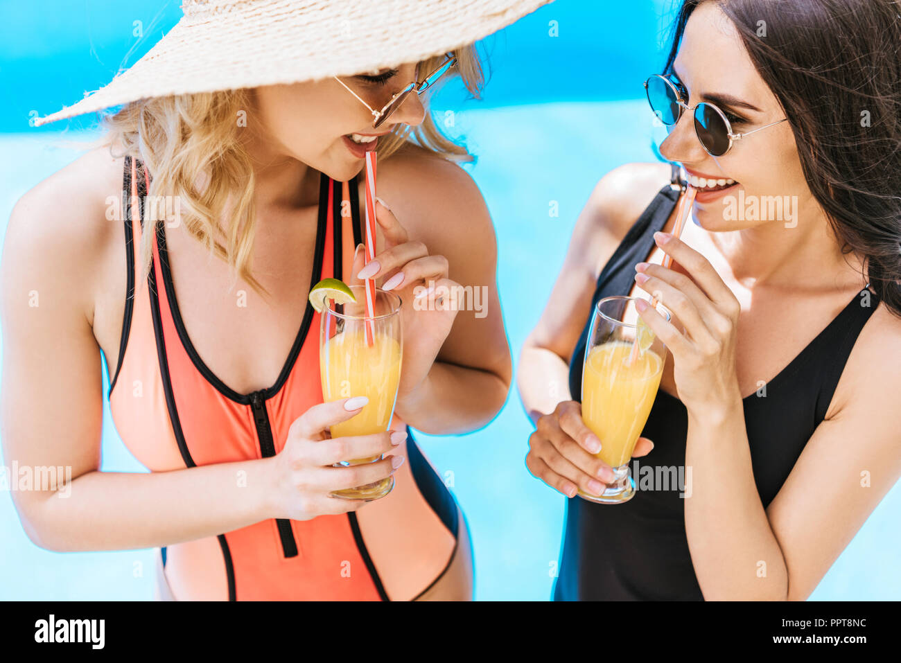 beautiful happy young girlfriends in swimsuits drinking cocktails at poolside - Stock Image