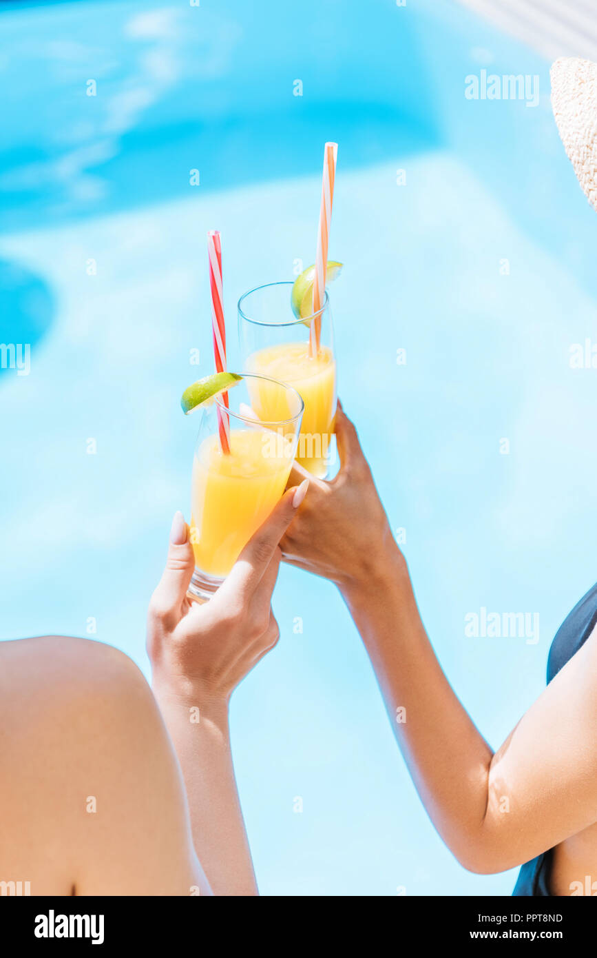 cropped shot of young women in swimwear and hats clinking glasses with refreshing beverages at pool - Stock Image