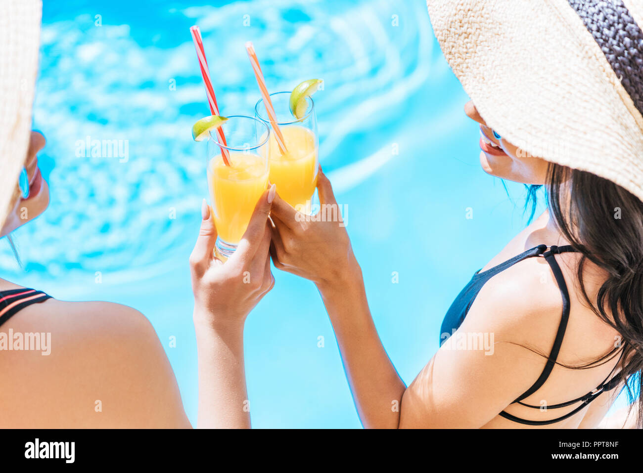 cropped shot of young women in swimwear and hats holding glasses with refreshing beverages at pool - Stock Image