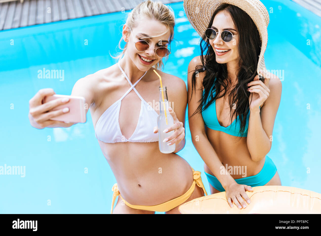 beautiful happy young girlfriends taking selfie with smartphone at poolside - Stock Image