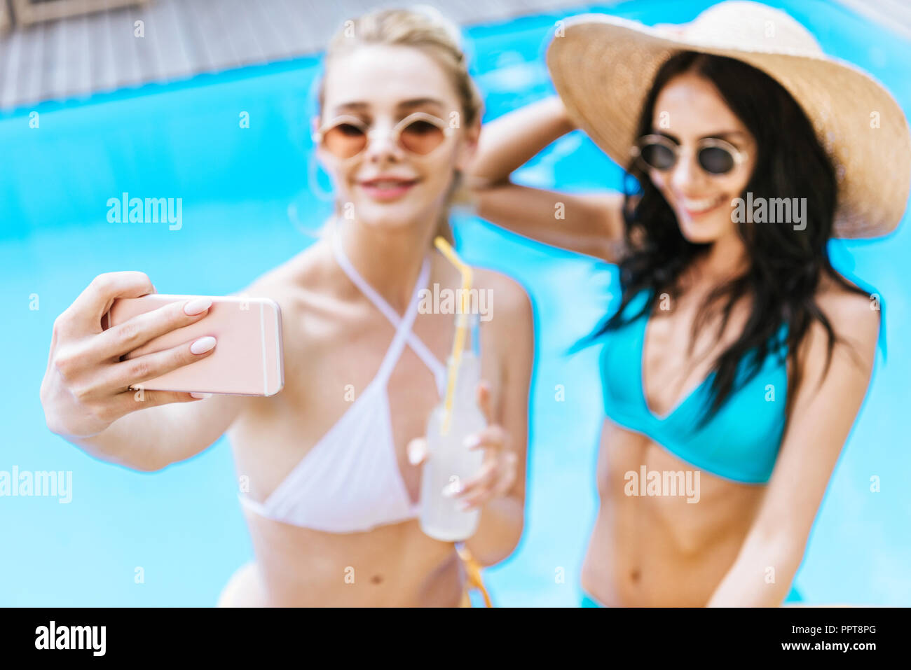 beautiful young girlfriends taking selfie with smartphone at poolside - Stock Image