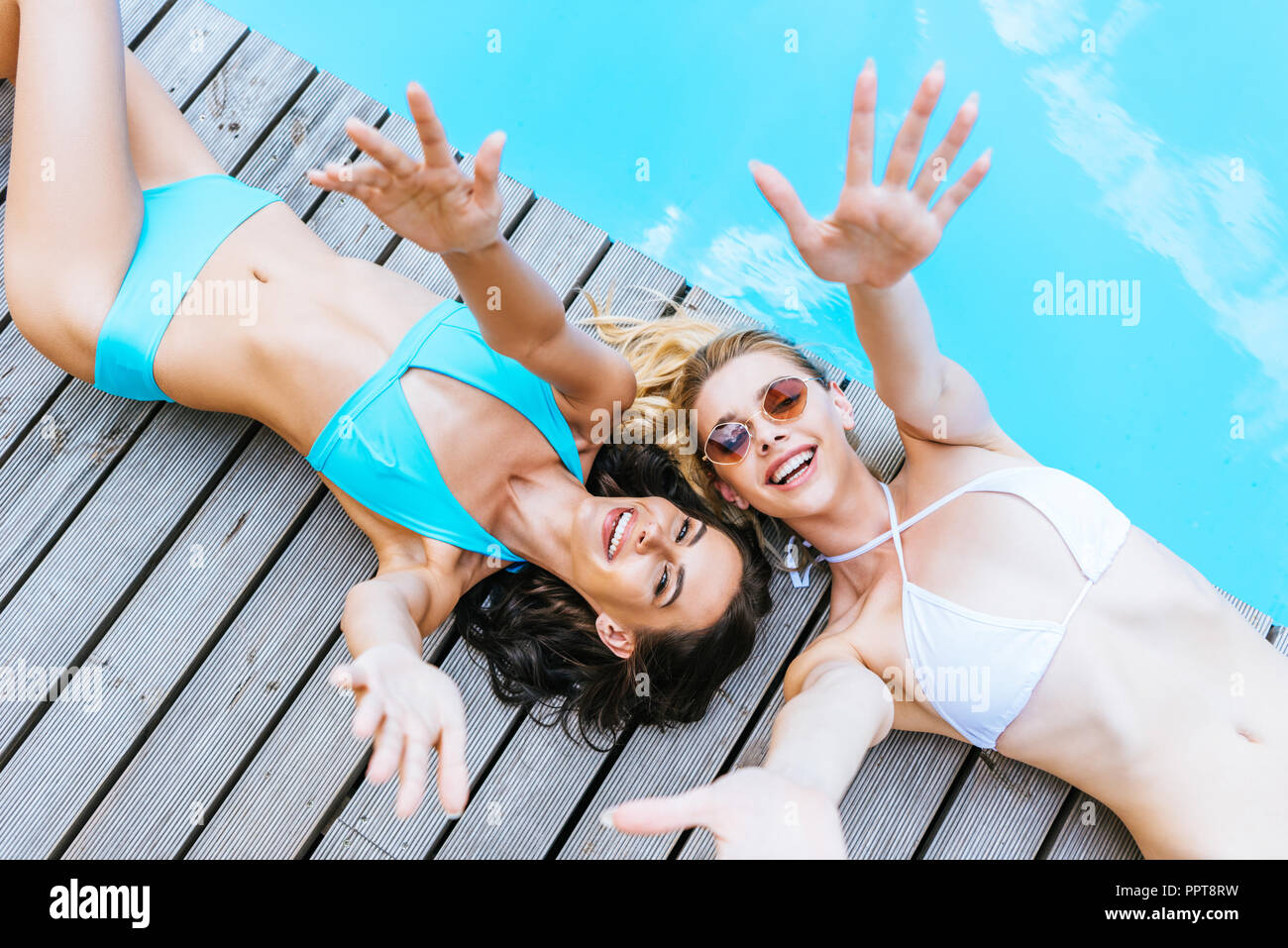 top view of happy young women in sunglasses and swimwear reaching arms and smiling at camera near pool - Stock Image