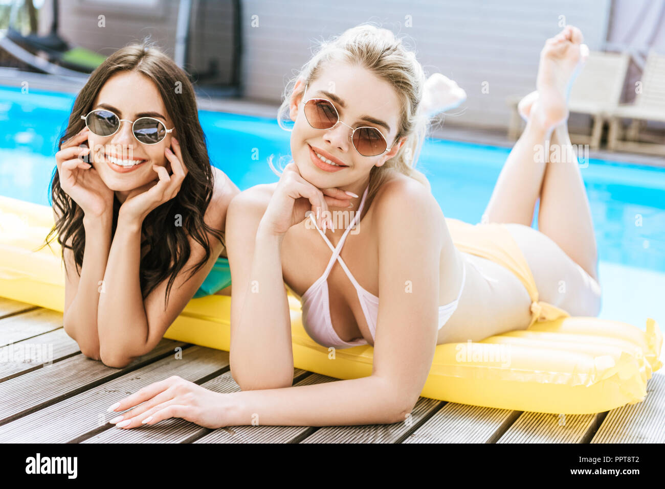 beautiful young women in sunglasses and swimwear lying on inflatable mattress and smiling at camera near swimming pool - Stock Image