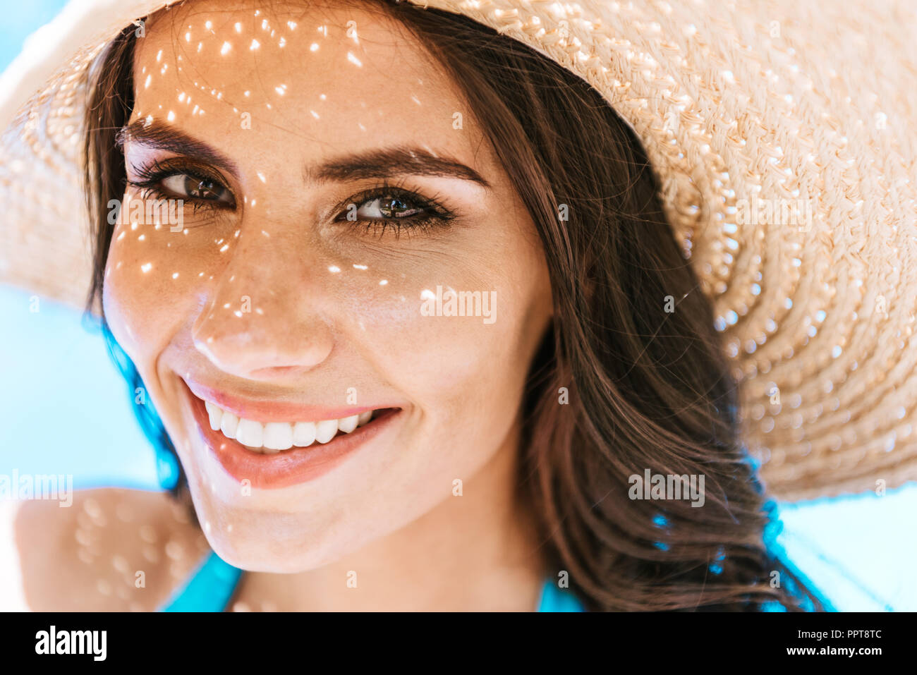 beautiful brunette woman in straw hat smiling at camera - Stock Image