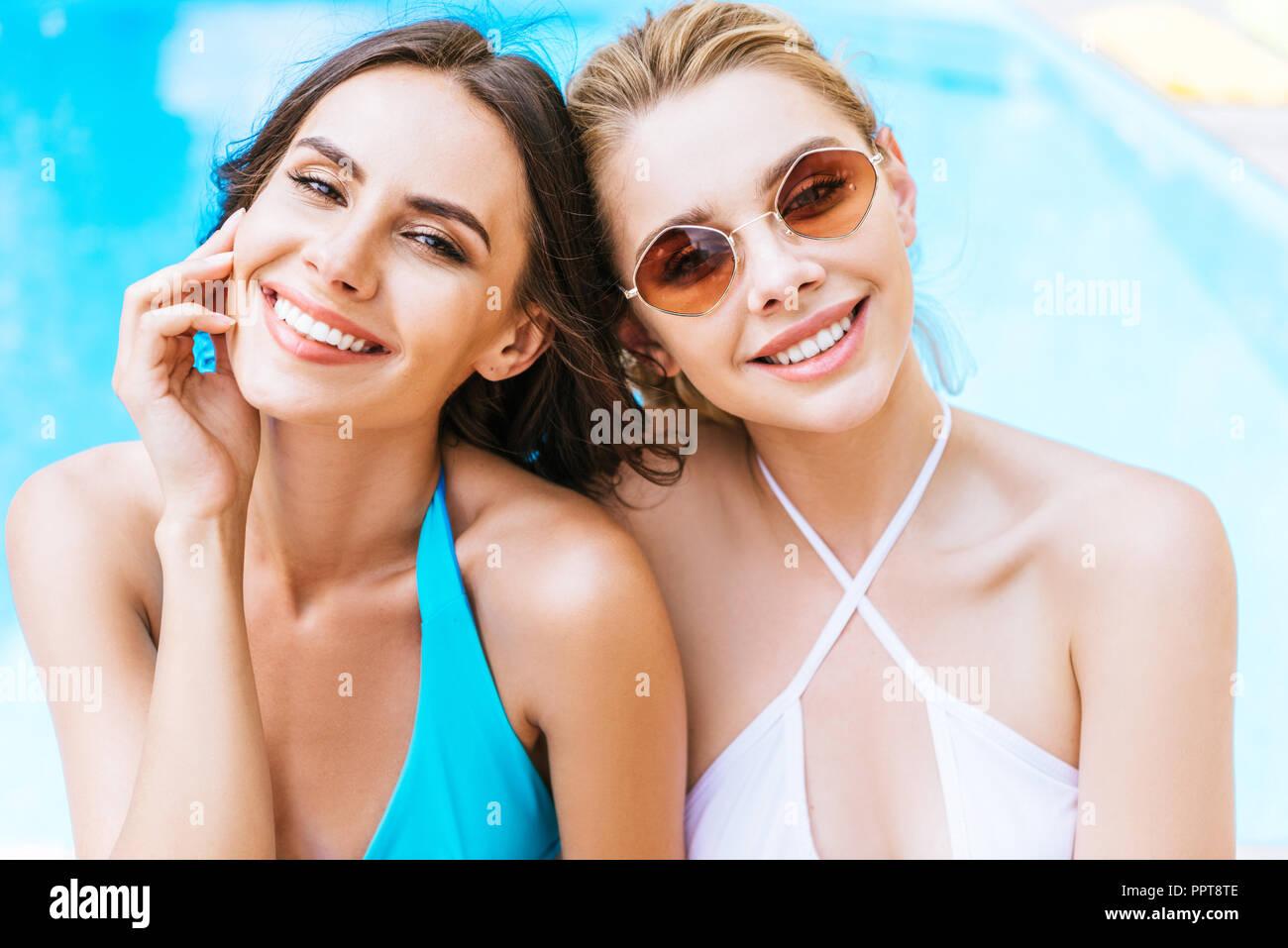 beautiful happy young women in swimwear smiling at camera near swimming pool - Stock Image