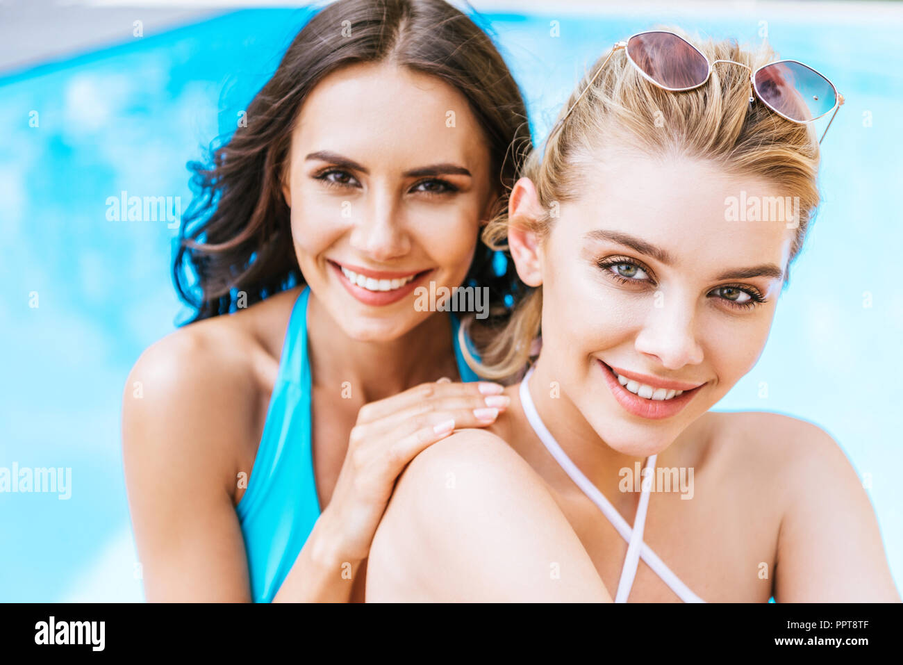 beautiful happy young girlfriends smiling at camera near swimming pool - Stock Image