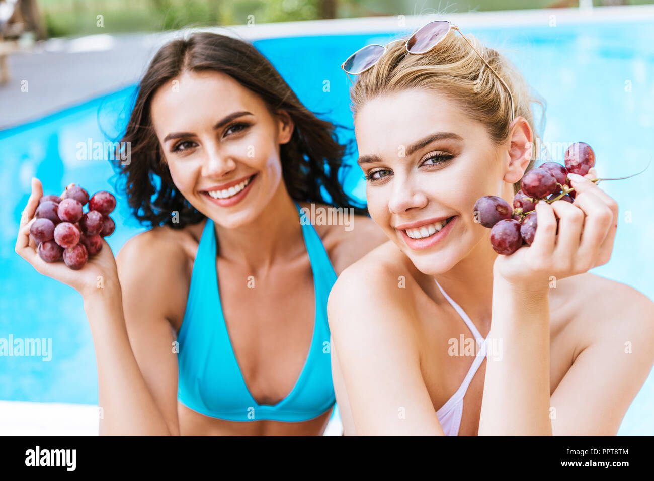 beautiful young women in swimwear holding fresh ripe grapes and smiling at camera at poolside - Stock Image