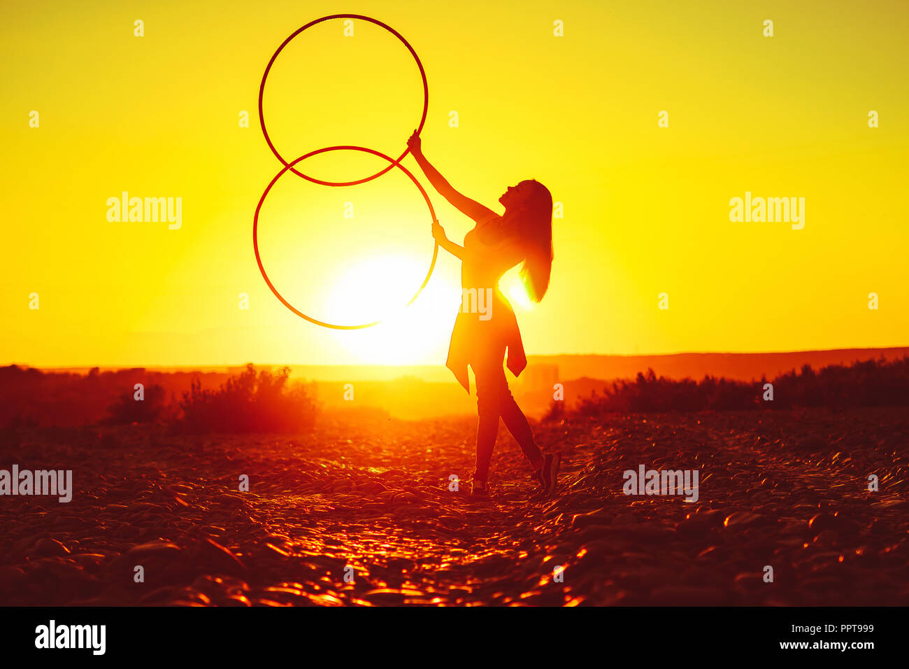 woman rotates hula hoop on nature background - Stock Image