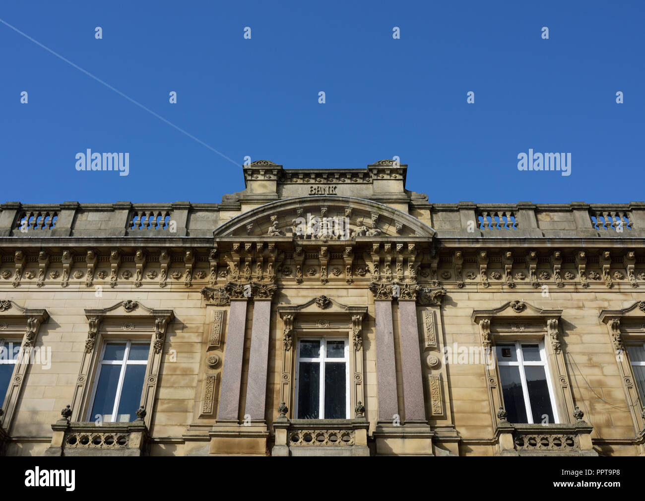 Old bank building, grade 11 listed former barclays bank, parapet and balustrade, with vapour trail in blue sky on silver street in bury lancashire uk - Stock Image