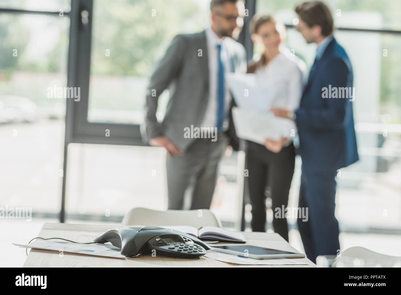 close-up shot of conference phone with blurred business people on background at office - Stock Image