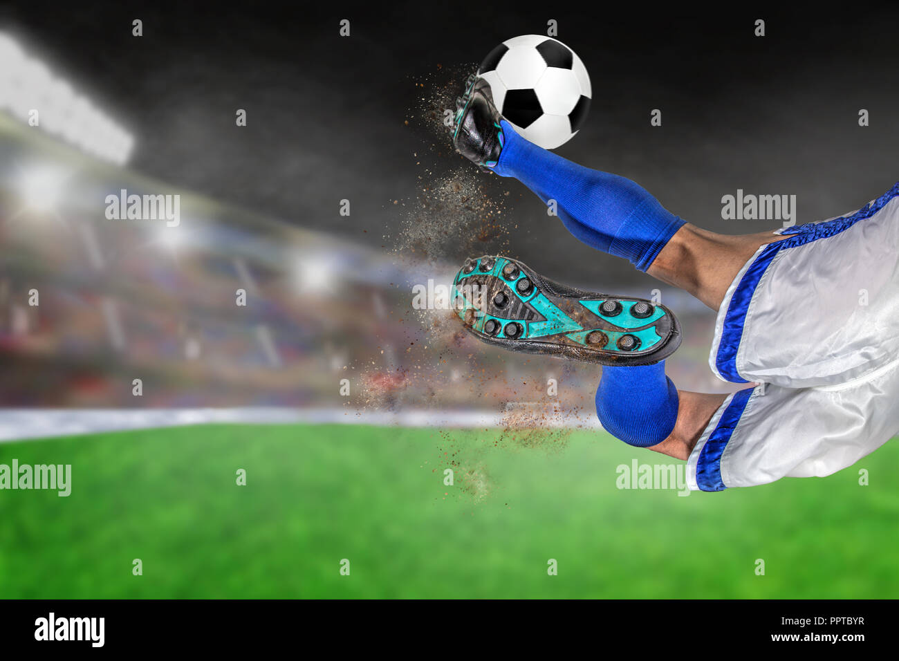 Soccer player with spectacular scissor kick of football in brightly lit outdoor stadium. Focus on foreground and soccer ball with shallow depth of fie - Stock Image