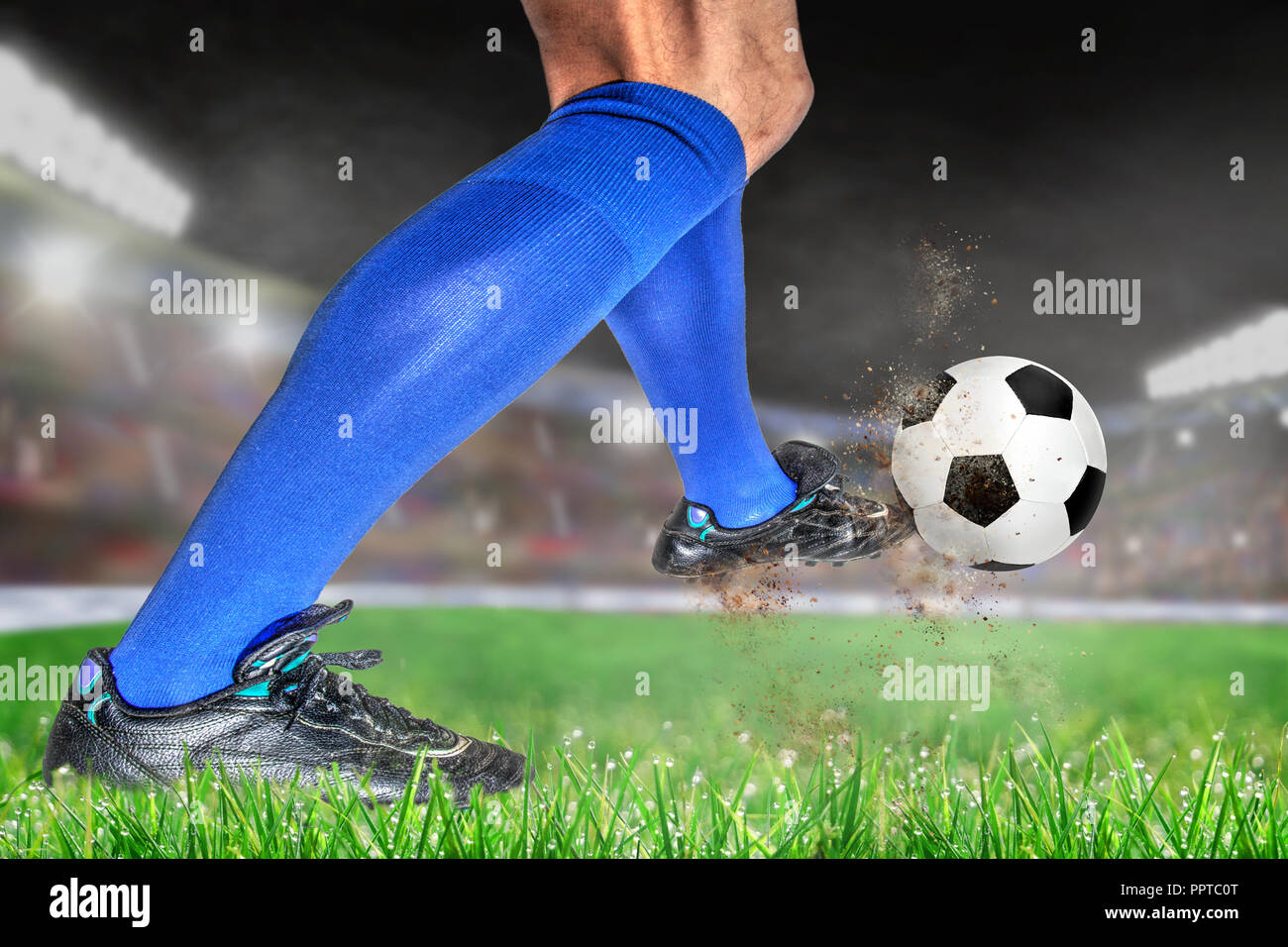 Soccer player in action with football in brightly lit outdoor stadium. Focus on foreground and soccer ball with shallow depth of field on background a - Stock Image
