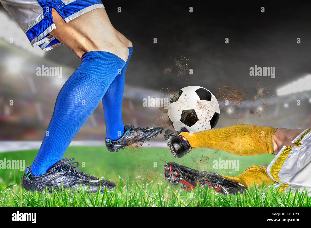 Soccer players in action with football in brightly lit outdoor stadium. Focus on foreground and soccer ball with shallow depth of field on background  - Stock Image