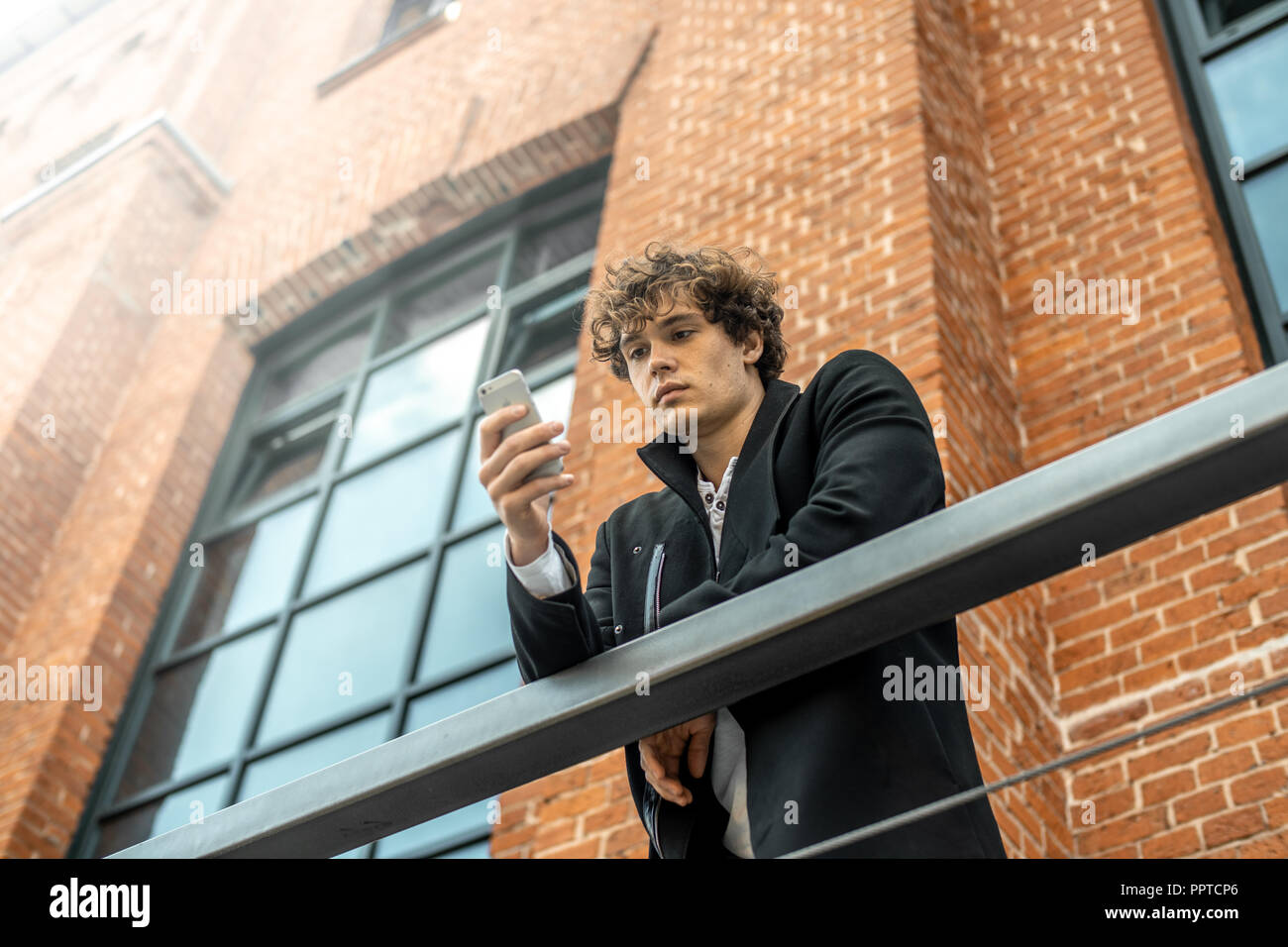 Attractive pensive man standing on staircase and looking at mobile phone screen. - Stock Image