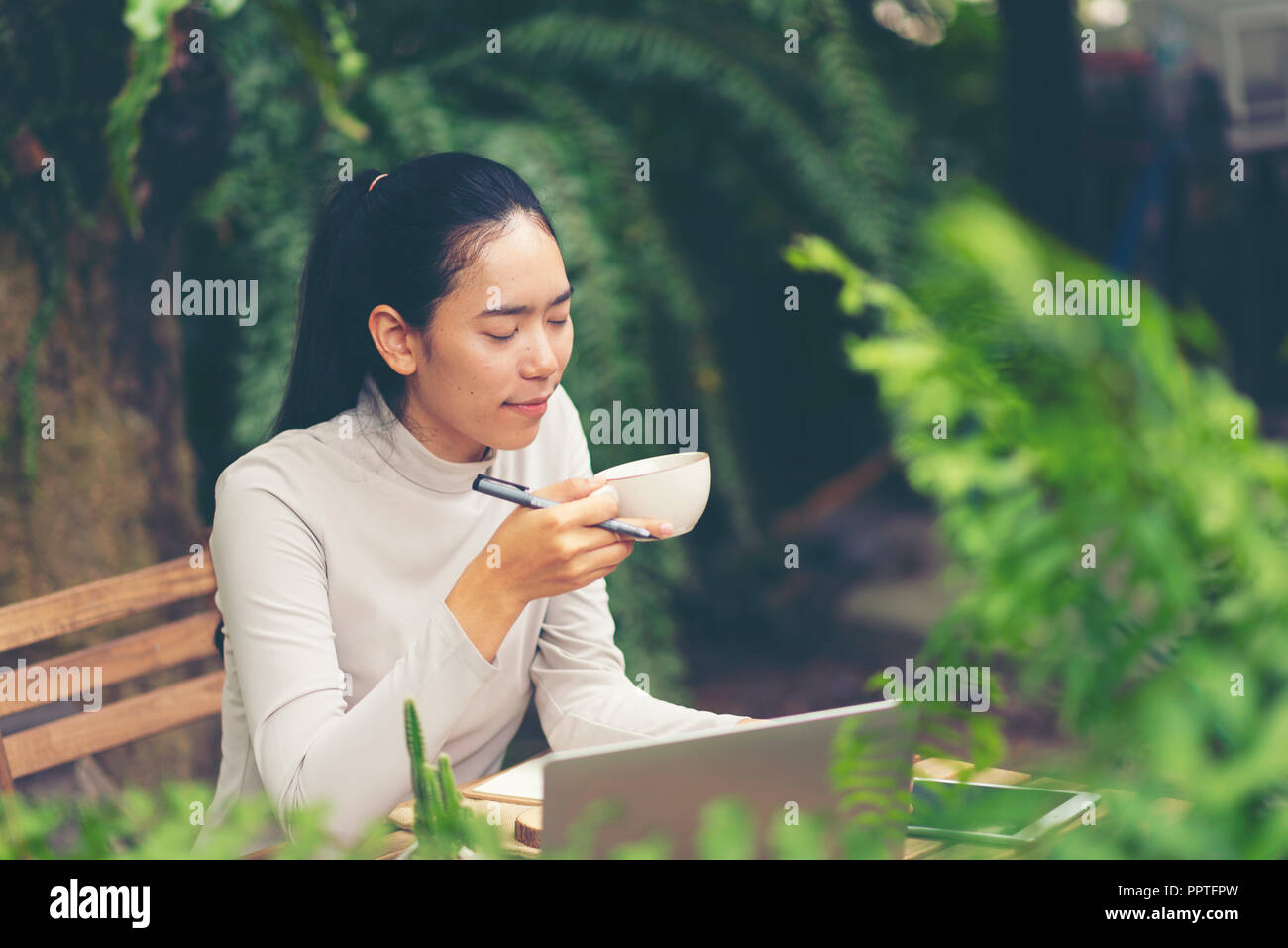 Charming pensive hipster girl looking away while enjoying aroma coffee and sitting at table. Contemplative business woman spending free time with tast - Stock Image