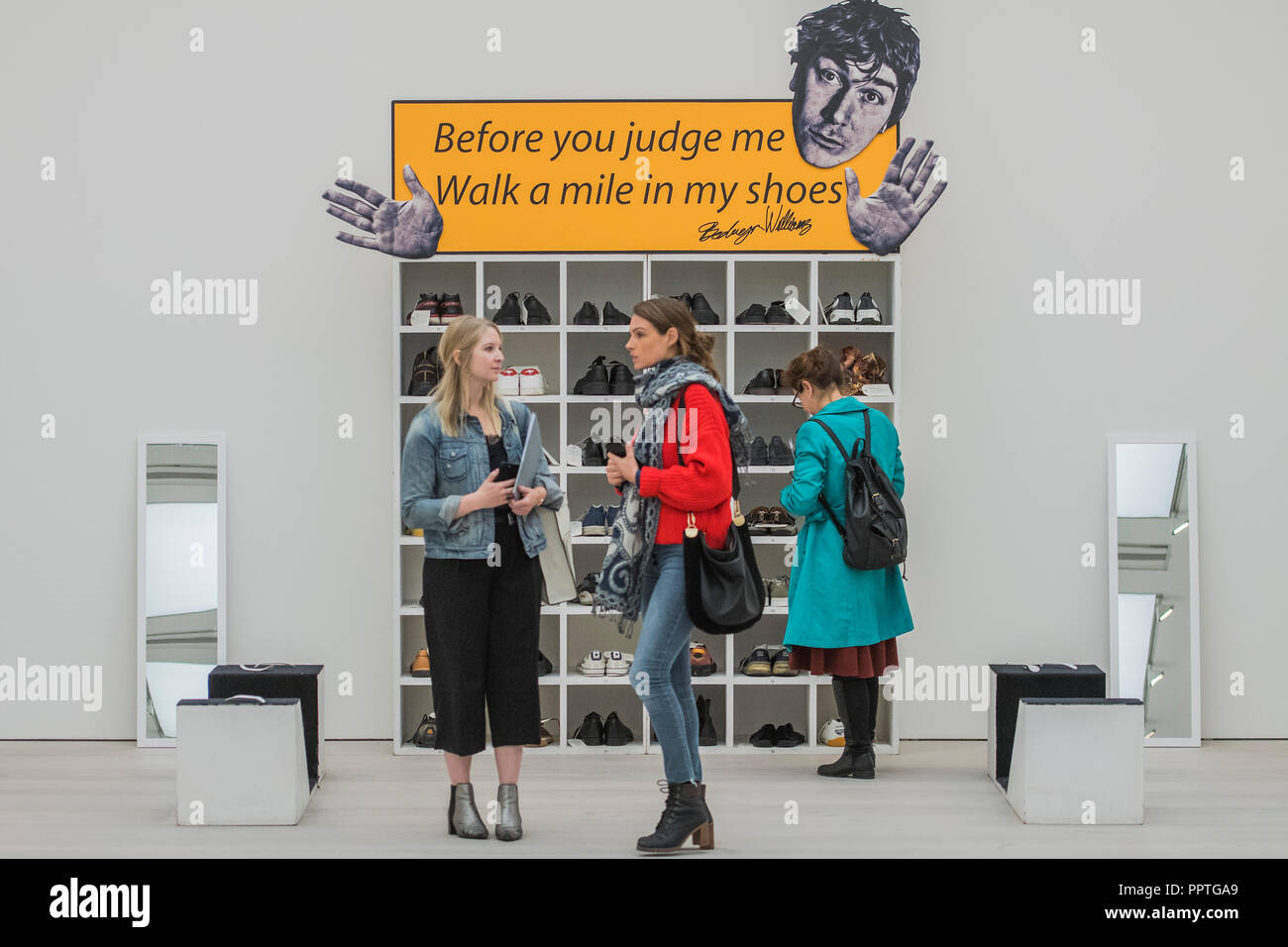 London, UK. 27th Sep 2018. Bedwyr Williams' Walk A Mile In My Shoes, a display case with 45 pairs of his own size 13 shoes. He invites the audience to share in his own 'problems of podietry ' by trying them on - Black Mirror the new exhibition at the Saatchi Gallery about art's role in social satire - featuring the work of 26 contemporary artists. It runs from 28 Sept 18 to 13 Jan 19. Credit: Guy Bell/Alamy Live News Stock Photo