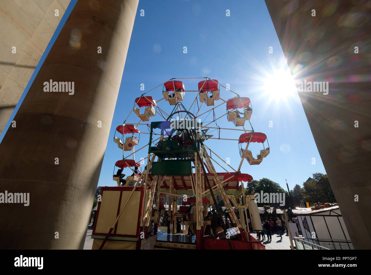 27 September 2018, Baden-Wuerttemberg, Stuttgart: In the bright sunshine on the Schlossplatz, an ancient chain carousel rotates through the columns of the king's building. The ride is part of the Historical Folk Festival, which is held on the occasion of the 200th anniversary of the Stuttgarter Wasen. Photo: Bernd Weißbrod/dpa - Stock Image