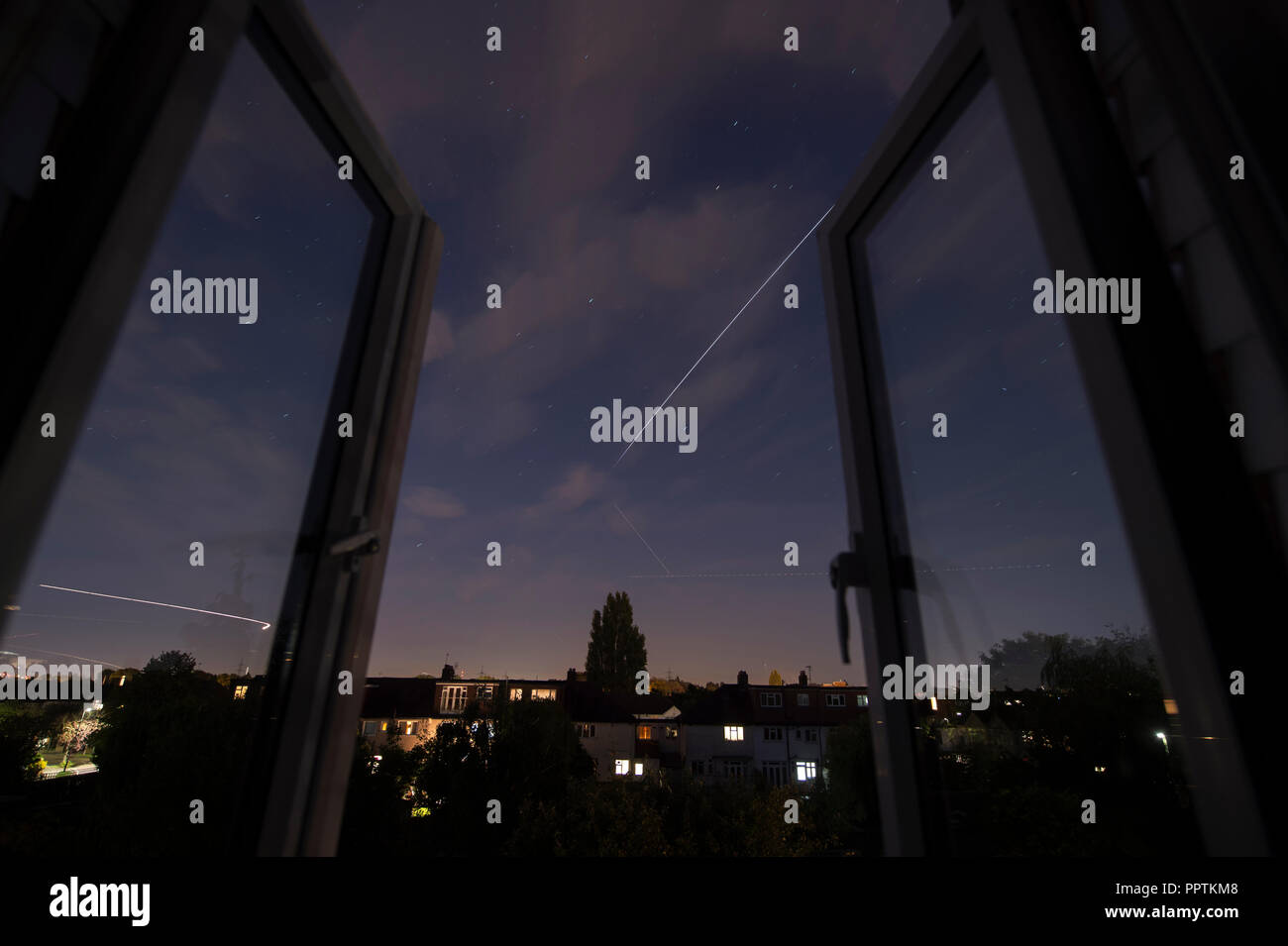 Wimbledon, London, UK. 27 September, 2018. Clear evening skies and an open window shows the International Space Station travelling overhead at 17,000 mph, brightly lit by sunlight hitting it's solar panels, gradually fading as it moves into Earth's shadow 22 degrees above due east and mingling with the much lower trails of aircraft heading to various London airports. Credit: Malcolm Park/Alamy Live News. - Stock Image