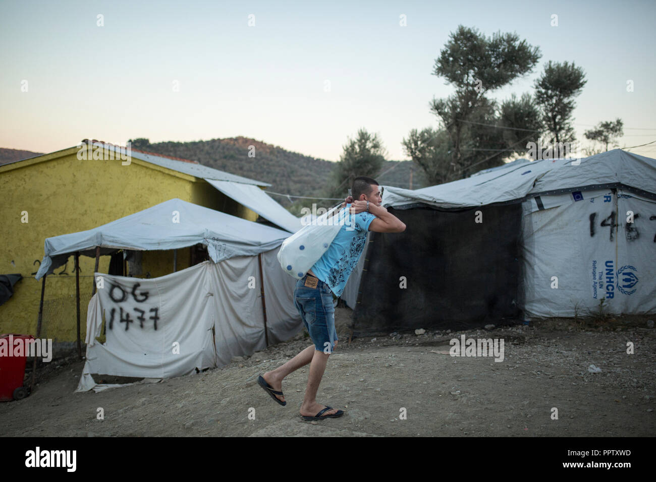Moira, Greece. 24th Sep, 2018. In a temporary camp next to the refugee camp Moria, a man carries a plastic bag filled with water bottles. (to dpa 'Moria: The camp of shame on the island of Lesbos' of 28.09.2018) Credit: Socrates Baltagiannis/dpa/Alamy Live News - Stock Image