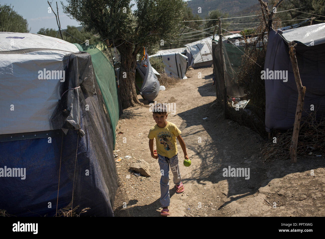 Moira, Greece. 24th Sep, 2018. A child walks between the tents in a temporary camp next to the refugee camp of Moria. Credit: Socrates Baltagiannis/dpa/Alamy Live News - Stock Image
