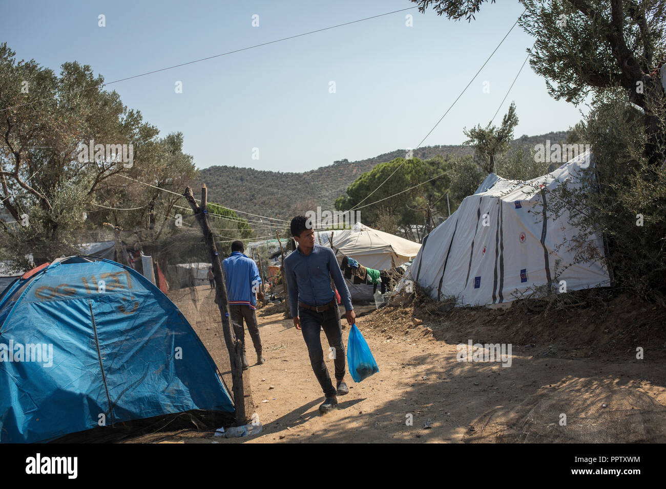 Moira, Greece. 24th Sep, 2018. A man walks between the tents in a temporary camp next to the refugee camp Moria. Credit: Socrates Baltagiannis/dpa/Alamy Live News - Stock Image