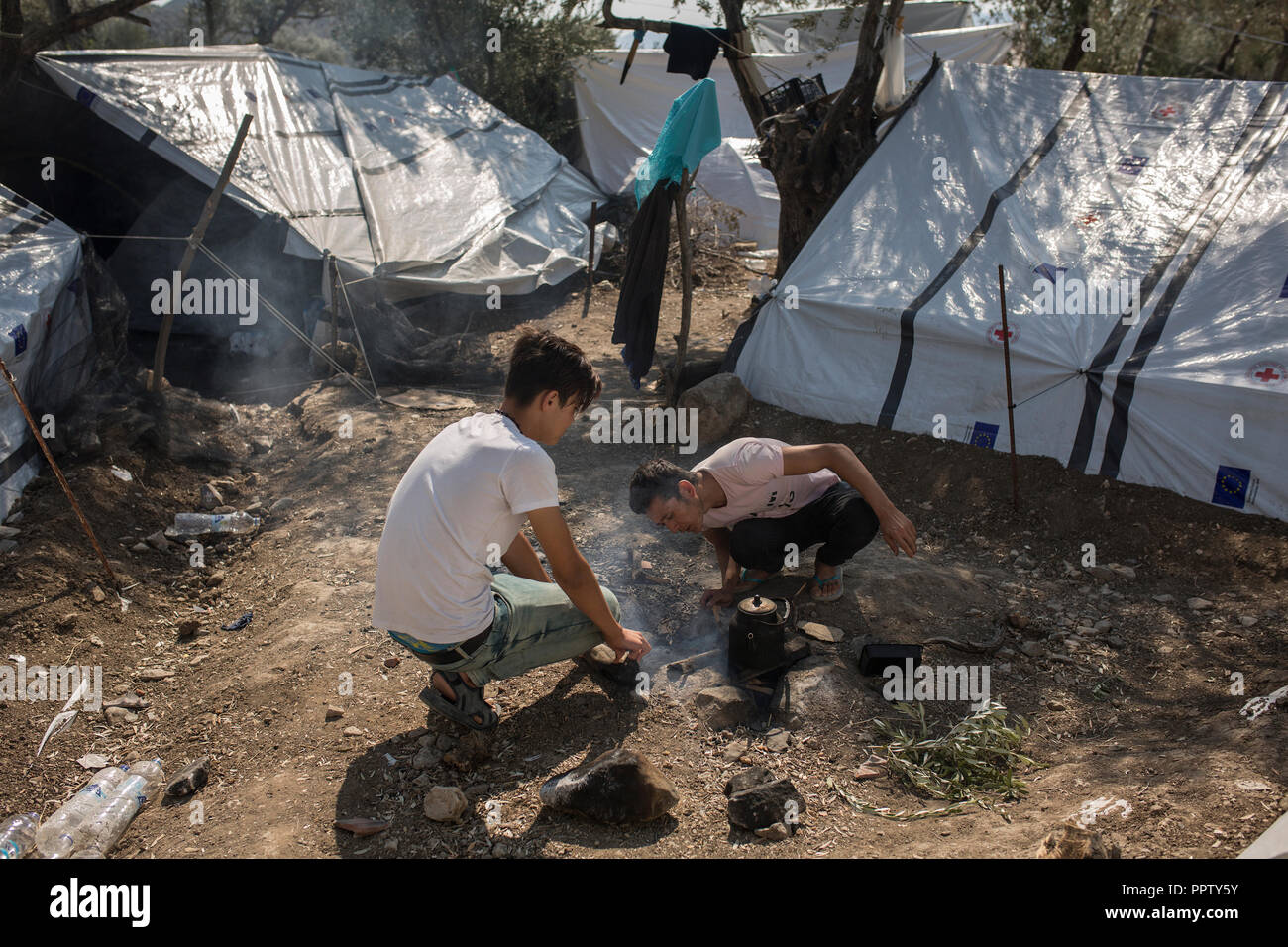 Moira, Greece. 25th Sep, 2018. Two young asylum seekers from Afghanistan prepare tea outside their tent in a temporary camp next to Moria's refugee camp. (to dpa 'Moria: The camp of shame on the island of Lesbos' of 28.09.2018) Credit: Socrates Baltagiannis/dpa/Alamy Live News - Stock Image