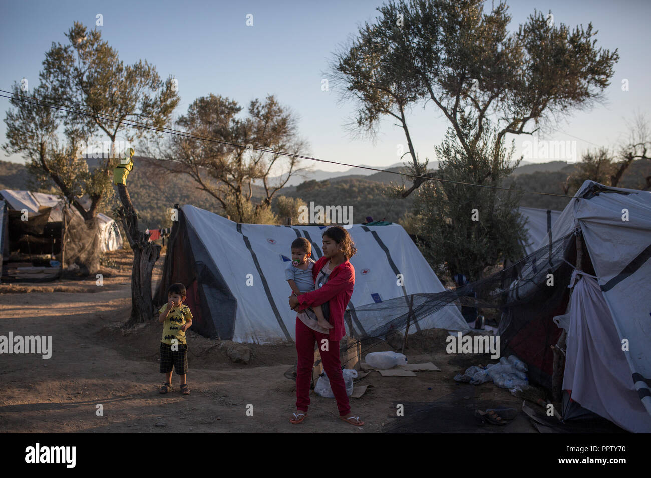 Moira, Greece. 24th Sep, 2018. Children stand between tents in a temporary camp next to the refugee camp of Moria. Credit: Socrates Baltagiannis/dpa/Alamy Live News - Stock Image