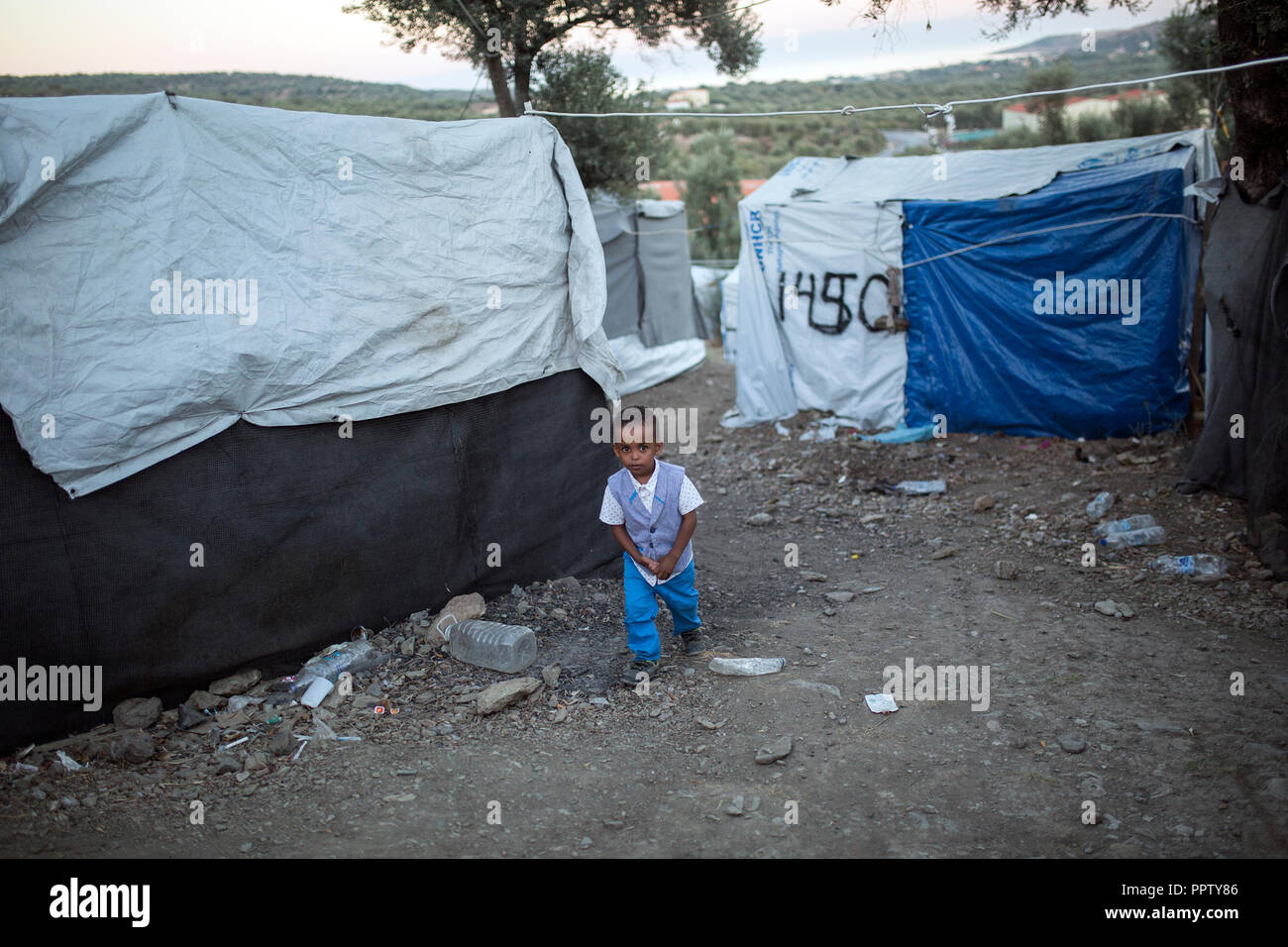 Moira, Greece. 24th Sep, 2018. A child walks between the tents in a temporary camp next to the refugee camp Moria. Credit: Socrates Baltagiannis/dpa/Alamy Live News - Stock Image