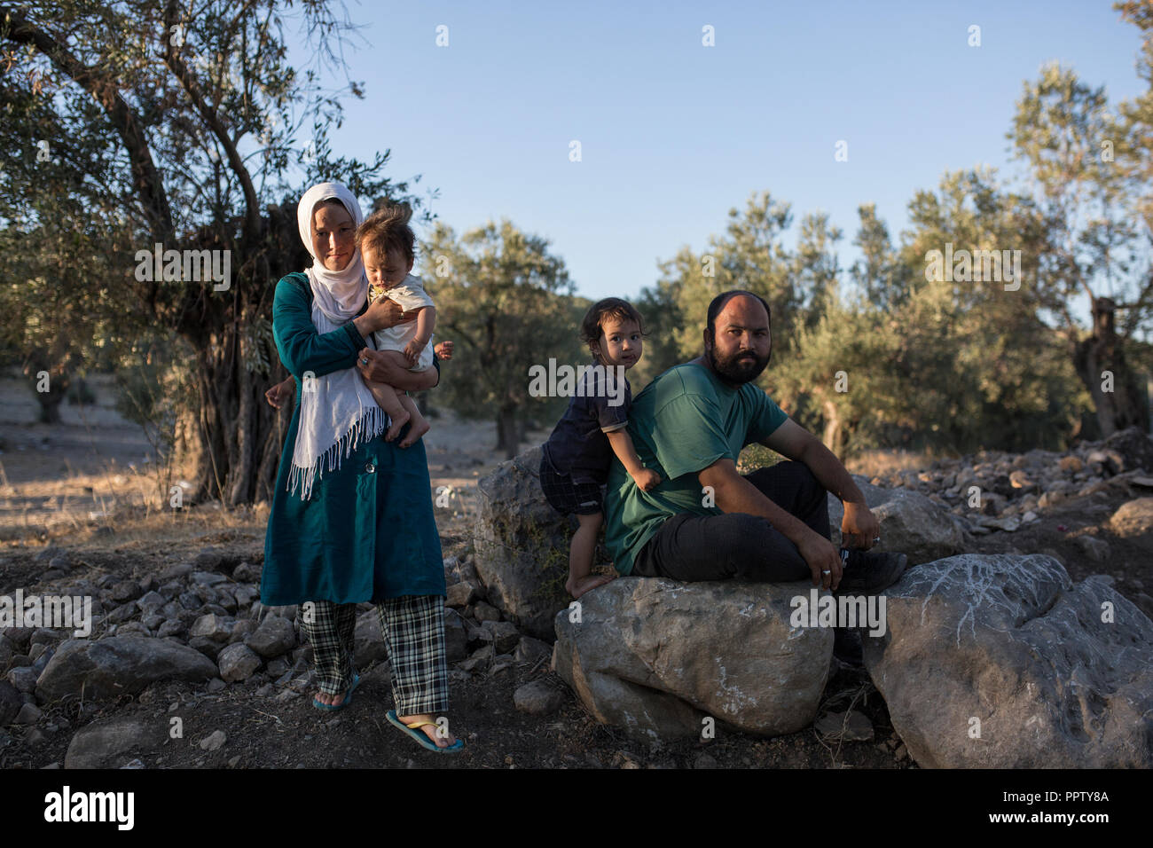 Moira, Greece. 24th Sep, 2018. A family is sitting in a temporary camp next to the refugee camp Moria. Credit: Socrates Baltagiannis/dpa/Alamy Live News - Stock Image