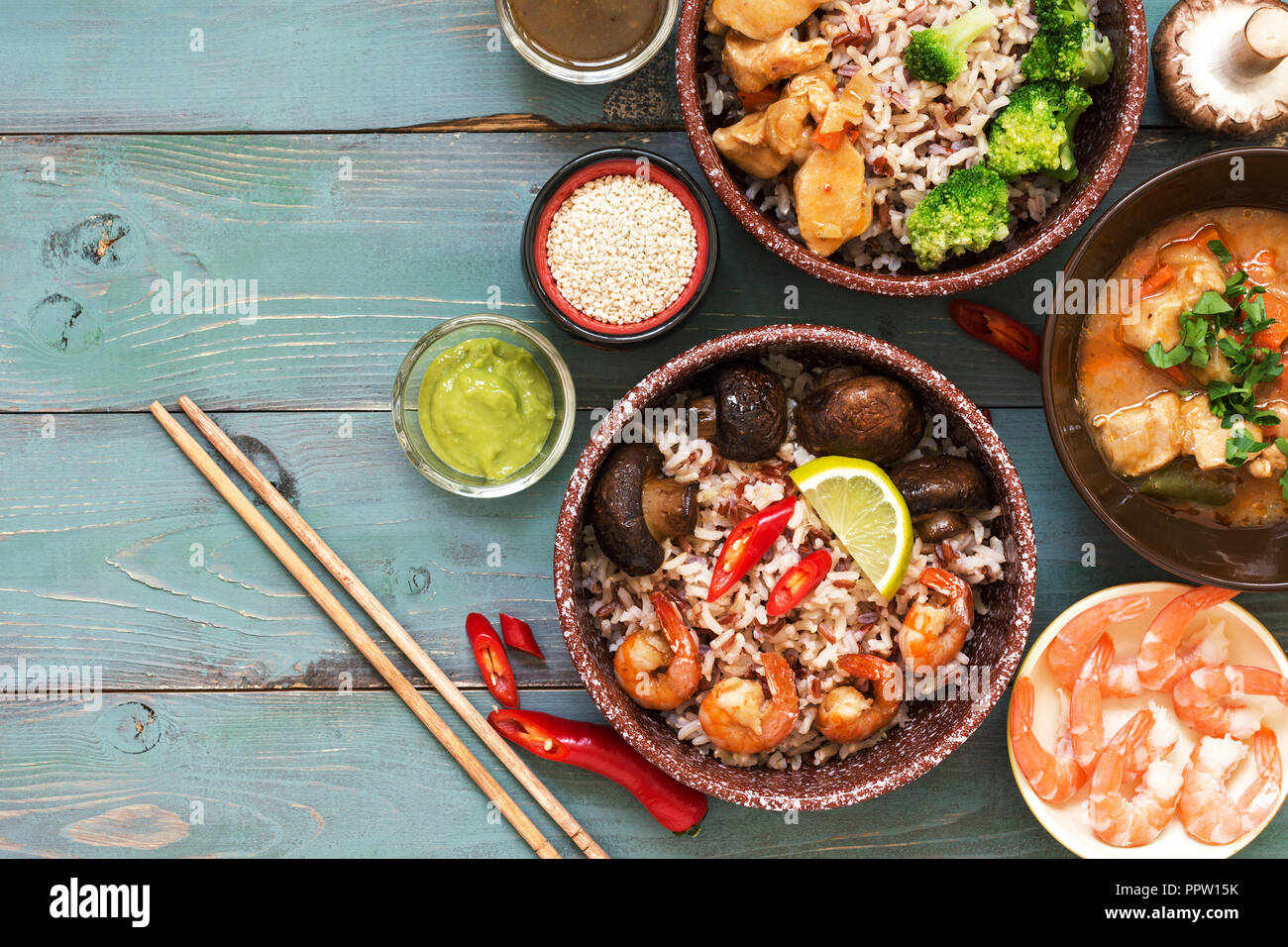 Asian food. Shrimp, rice, mushrooms, broccoli, stewed chicken, sauces on a rustic wooden background. Top view, space for text Stock Photo