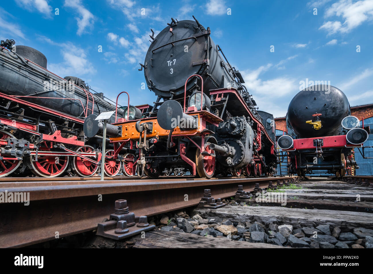 Jaworzyna Slaska, Poland - August 2018 : Man with a child looking at the old disused retro train locomotives and carriages on the side tracks in the d - Stock Image