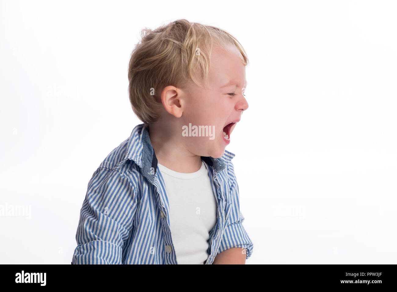 A profile view of a two year old boy crying. Shot in the studio on a white, seamless backdrop. - Stock Image