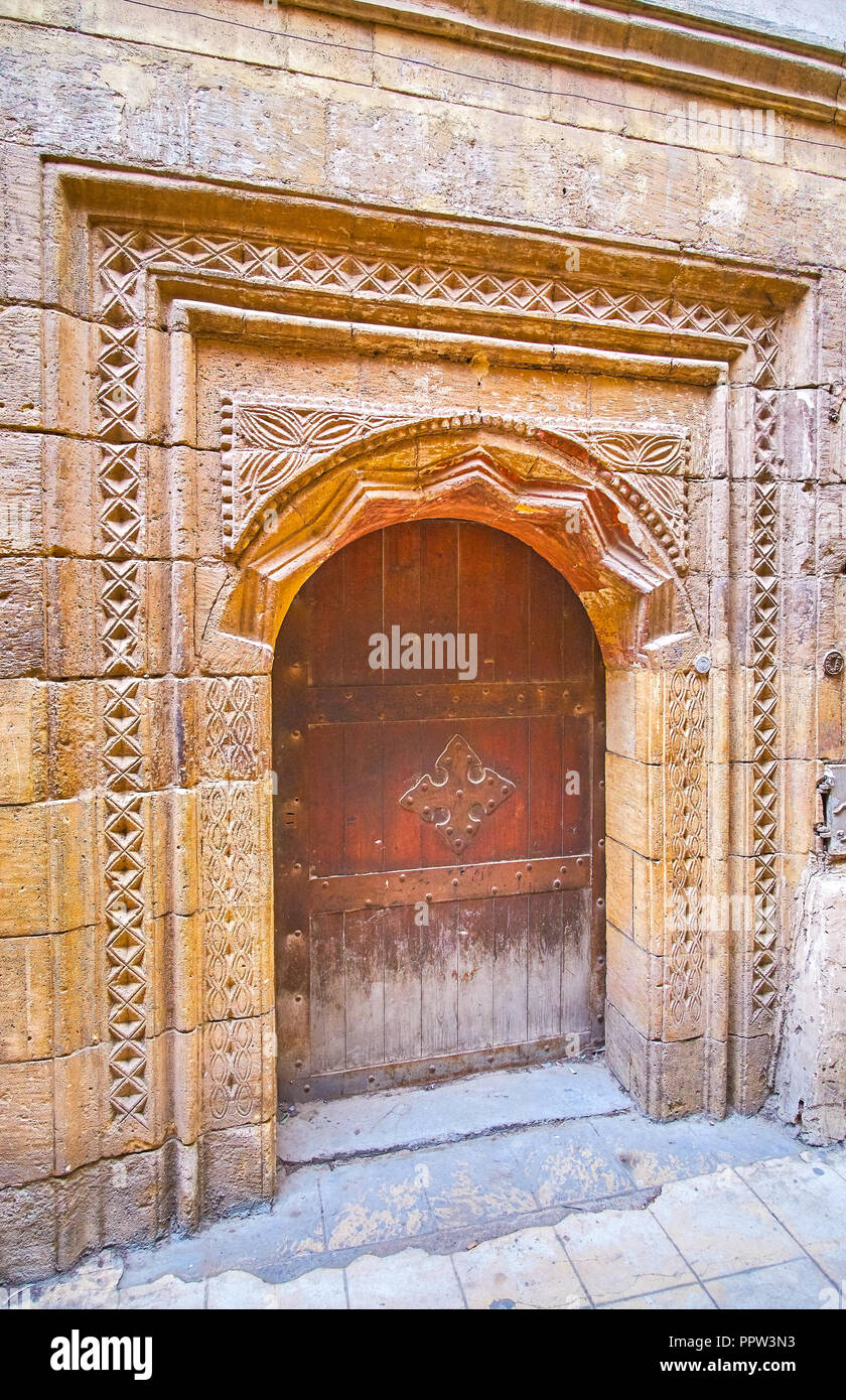 The medieval carved stone doorframe with metal cross on the door of the old edifice, in Coptic district of Cairo, Egypt - Stock Image