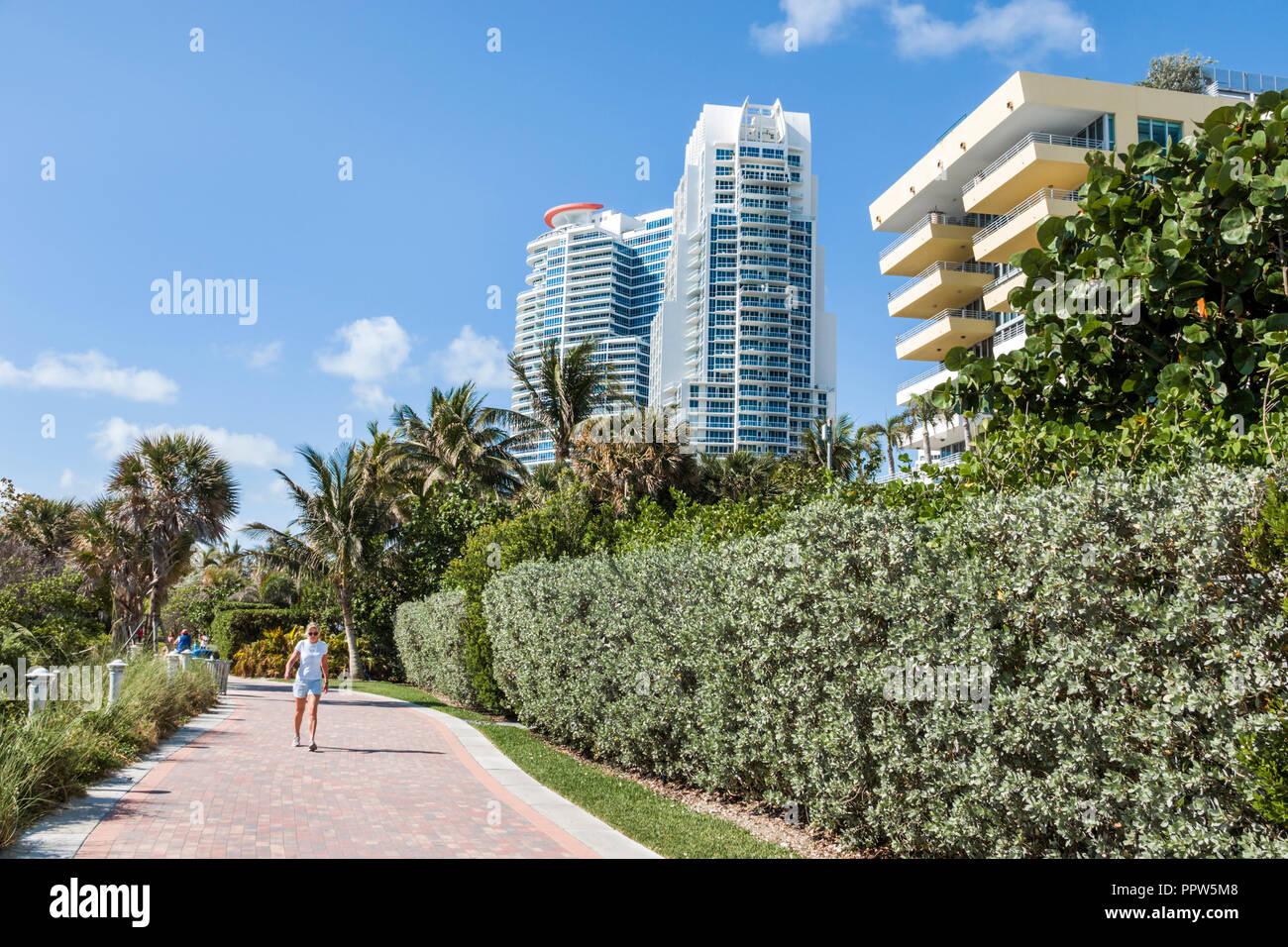 Miami Beach Florida South Pointe BeachWalk walk woman exercising Continuum high rise luxury condominium building buildings - Stock Image