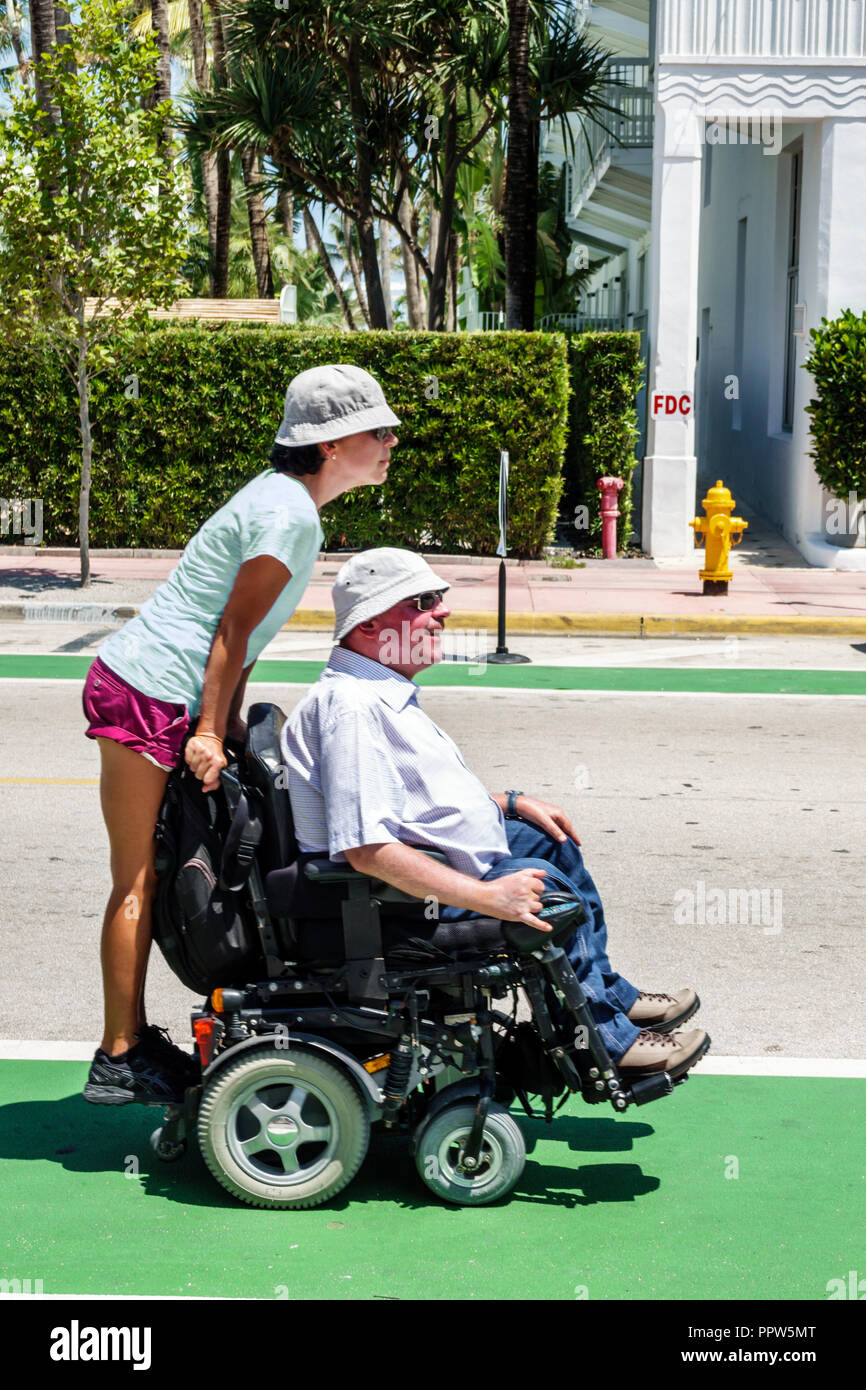 Miami Beach Florida disabled electric wheelchair man woman couple - Stock Image
