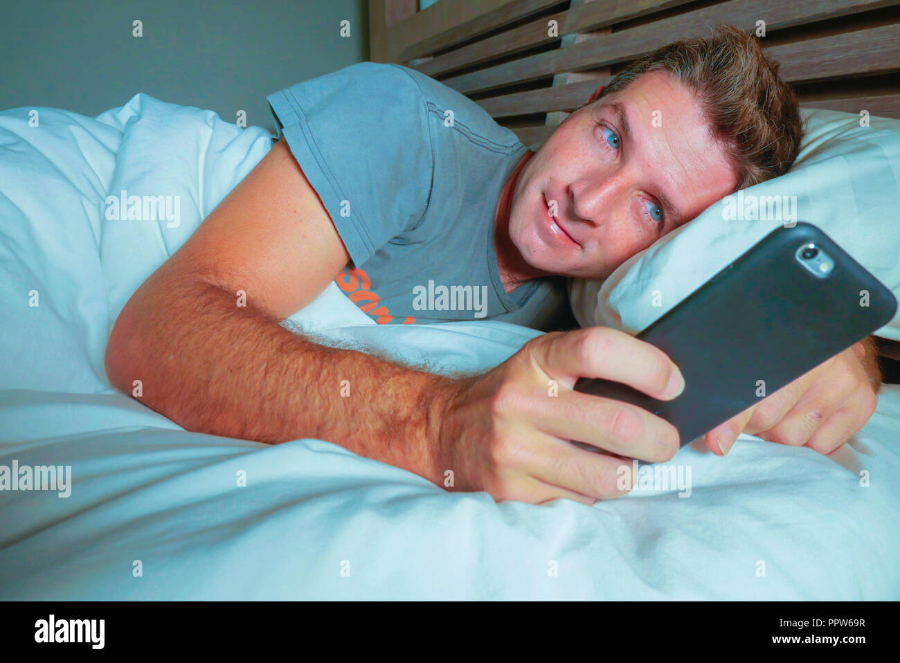 young attractive man smiling happy lying on bed at night using social media app on mobile phone texting or having video call in communication lifestyl - Stock Image