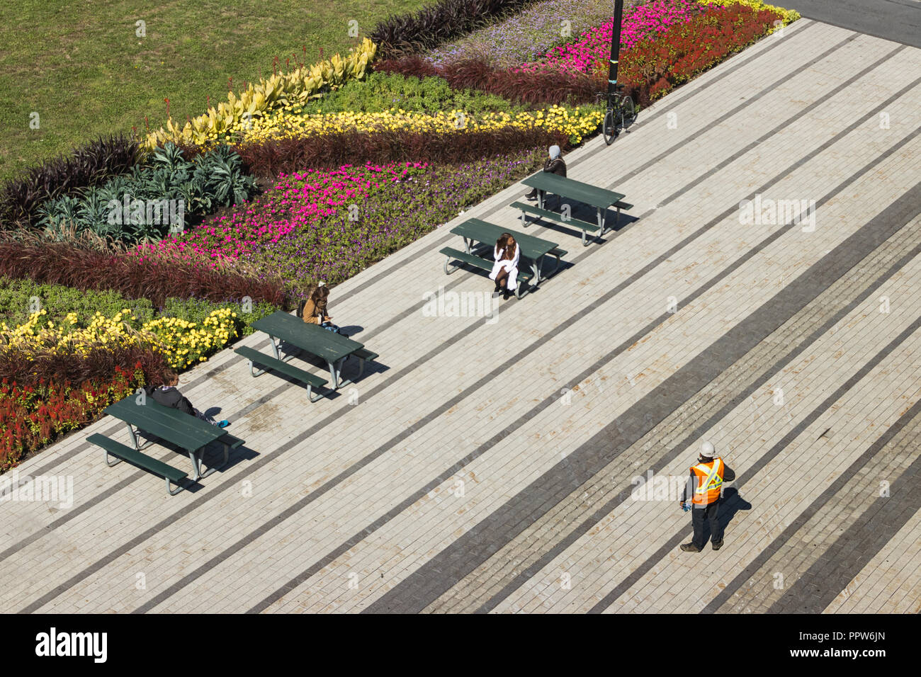 Urban scene with construction worker and people sitting at pik-nik tables in town. Urban Landscaping - flower ans plants in Summer. Bike attached to a - Stock Image