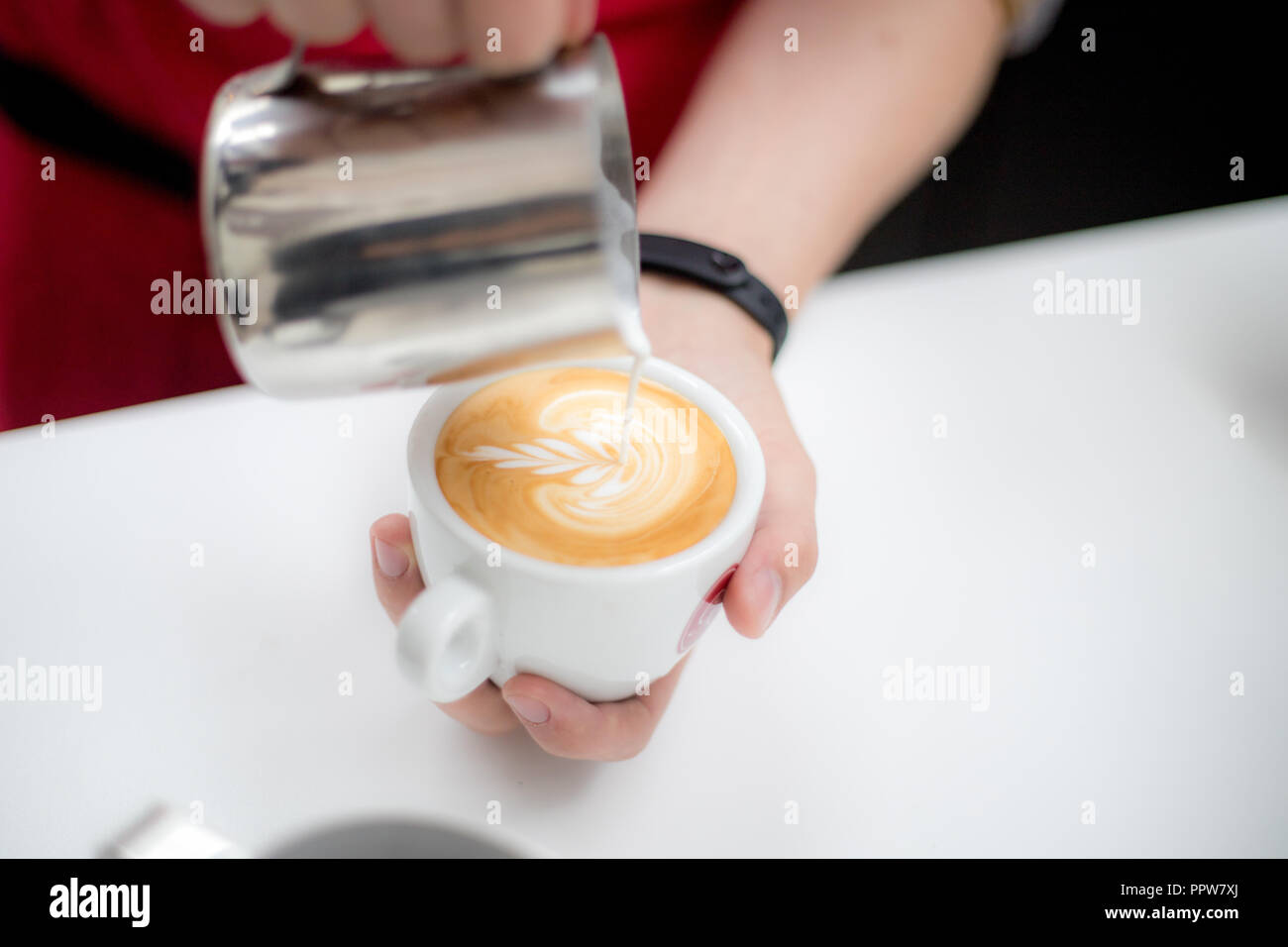Barista pours a cup of latte coffee and creates a beautiful image - Stock Image