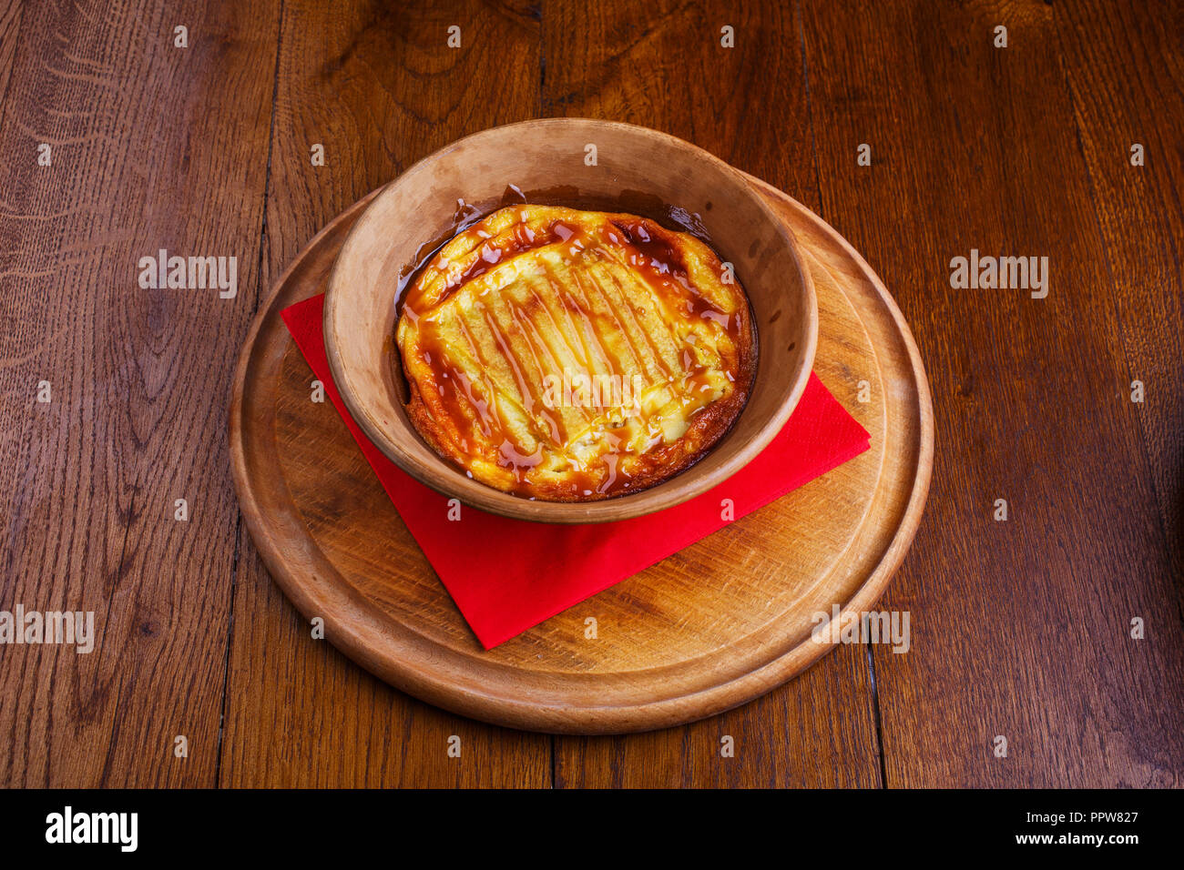 Sweet rice pudding baked in pottery. Sweet dish at the restaurant. Pudding with caramel - Stock Image