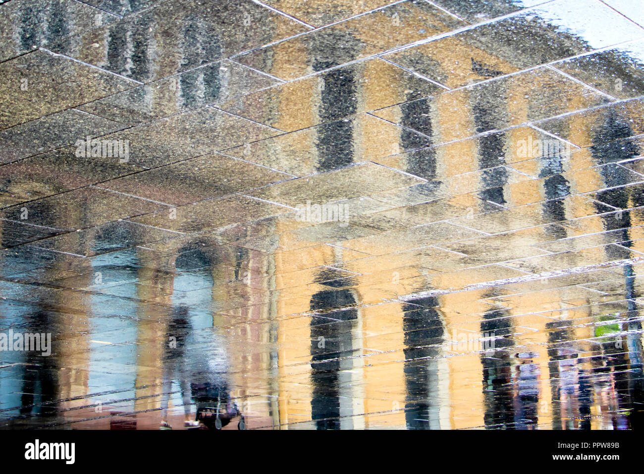 Blurry reflection shadow silhouette in a puddle of people walking on rainy city street Stock Photo