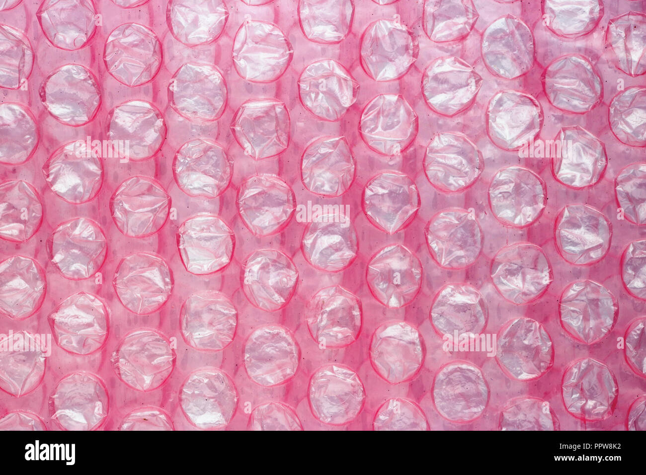 Layer of red used soft packaging film with burst dirty air bubbles. Studio macro background - Stock Image