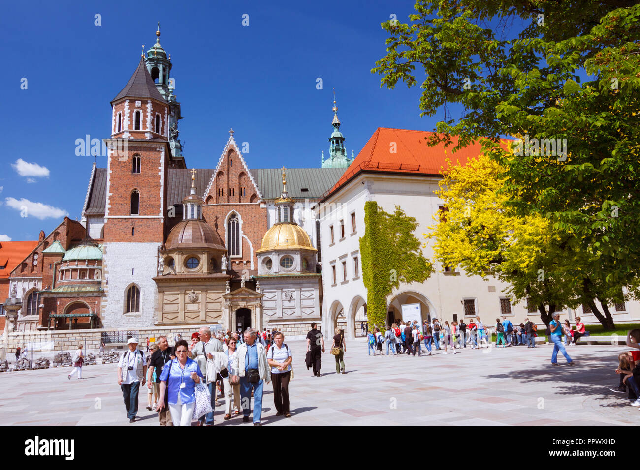 Krakow, Poland : Tourists walk around Wawel Cathedral on the Wawel Hill. First built and destroyed in the 11th century; the construction of the curren - Stock Image